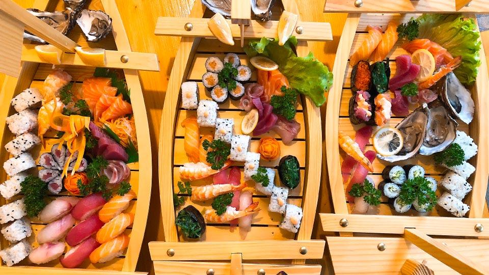 Barche di sushi con nigiri uramaki hosomaki e sashimi